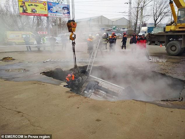 """Theo Daily Mail, vụ tai nạn hi hữu xảy ra ngày 19/11 tại một bãi gửi xe ở thành phố Penza (Nga), khi mặt đất đột nhiên nứt toác, """"nuốt trọn"""" một chiếc xe hơi cùng 2 người đàn ông ngồi trên xe xuống hố nước nóng."""