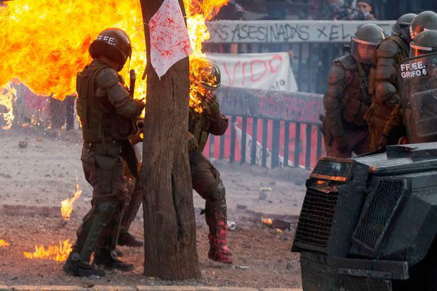 Nữ đặc nhiệm Chile bị ném bom xăng, gào thét đau đớn - Ảnh 1.