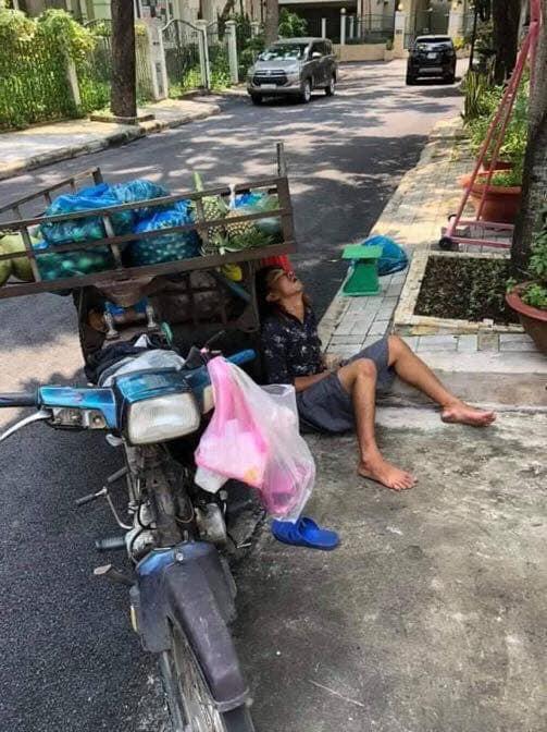 Anh bán hoa quả ngủ gục bên lề đường, tay vẫn cầm xấp tiền lẻ khiến nhiều người xót xa - Ảnh 1.