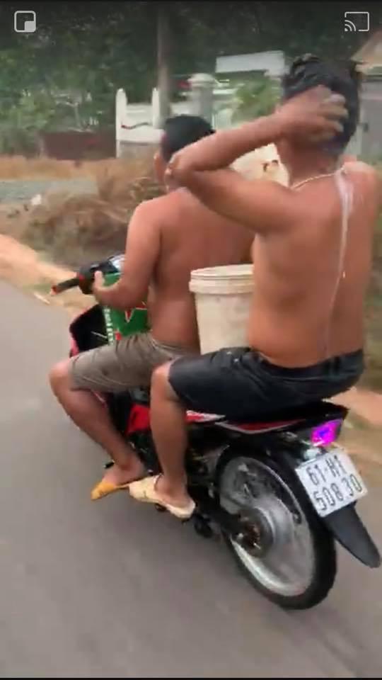 Hai thanh niên vừa chạy xe máy vừa tắm bị xử phạt 3,2 triệu đồng - Ảnh 1.