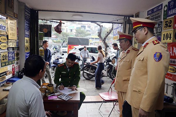 Kiểm tra cửa hàng trên phố Trần Nhật Duật, thu giữ hàng chục BKS giả - Ảnh 1.