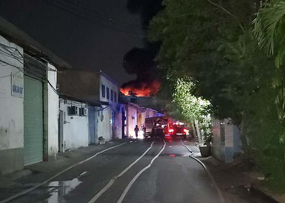 Cảnh sát dùng thang leo lên tầng nhà khống chế đám cháy lớn, thiêu rụi 6 tấn vải vụn trong đêm ở Sài Gòn - Ảnh 1.