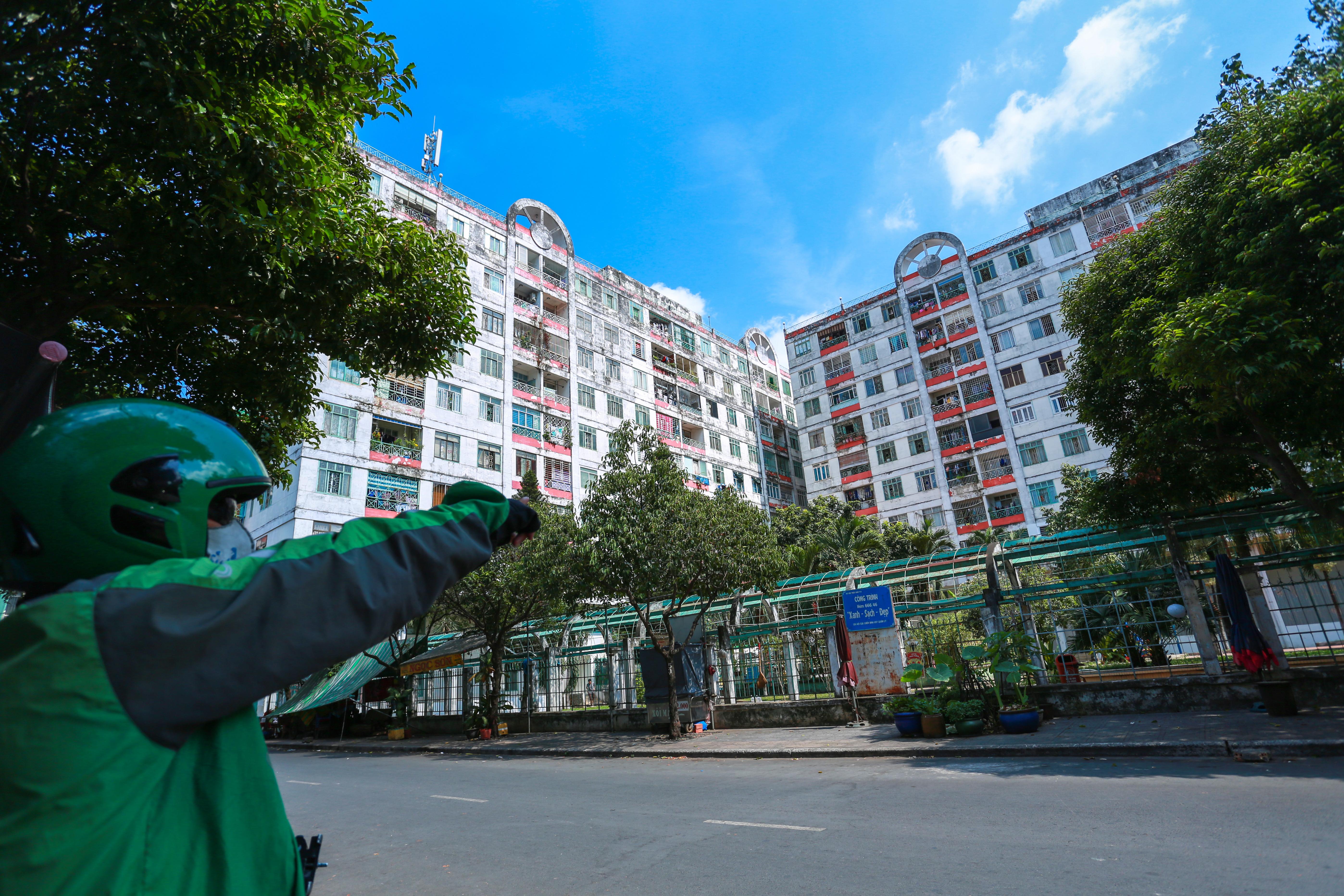 [ẢNH] Phong toả chung cư có ca nhiễm Covid-19 thứ 48 ở Sài Gòn, cư dân nhận tiếp tế lương thực qua hàng rào - Ảnh 1.