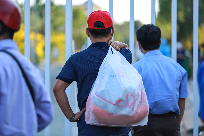 Sau lệnh cấm, nhiều người vẫn lén ném đồ tiếp tế qua hàng rào ở KTX ĐH Quốc gia TP. HCM - Ảnh 4.