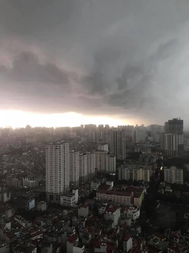 Hà Nội 2h chiều trời tối như ban đêm: Mây đen cuồn cuộn giăng kín bầu trời cùng mưa giông bất chợt khiến người dân phải bật đèn xe di chuyển - Ảnh 4.