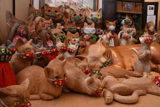 Ngôi đền đặc biệt ở Nhật Bản được mệnh danh là Đền Mèo, trụ trì tự tay làm khẩu trang cho hàng trăm chú mèo gỗ từ tã lót trẻ em - Ảnh 1.