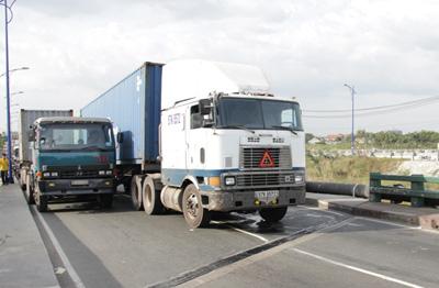 Chiếc container chắn giữa cầu khiến các xe tải khác phải nhích lên từng chút một.