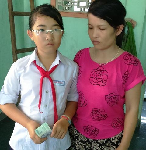 chị Võ Thị Hồng và bé Hồ Minh Hiếu xúc động nhận số tiền các nhà hảo tâm trao tặng
