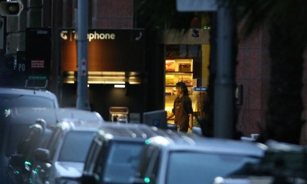 Một nhân viên đi lại gần cửa và tắt đèn bên trong quán cafe.