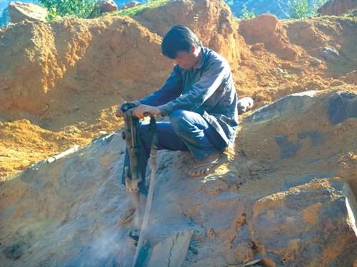 Một thợ khoan đang cố gắng tách hòn đá có đường kính chừng 3 mét.
