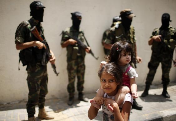 Một bé gái người Palestine cong em trên vai khi đi qua các chiến binh vũ trang ở Beit Lahiya, Dải Gaza.