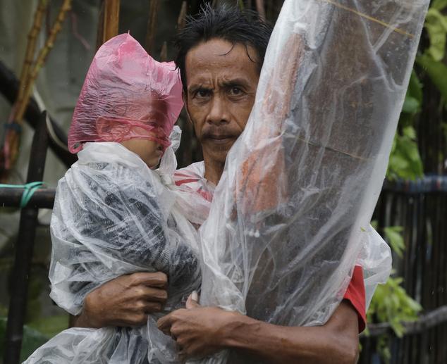Bố bế con trai nhỏ đi sơ tán dưới trời mua và gió mạnh ở Manila.