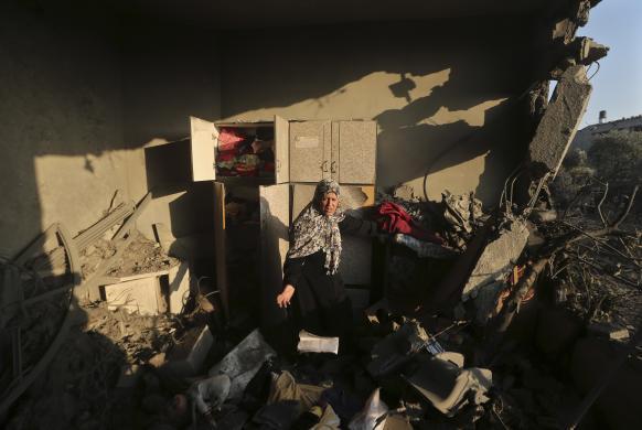 Một phụ nữ Palestine kiểm tra ngôi nhà bị phá hủy trong cuộc không kích của quân đội Israel tại thành phố Gaza.