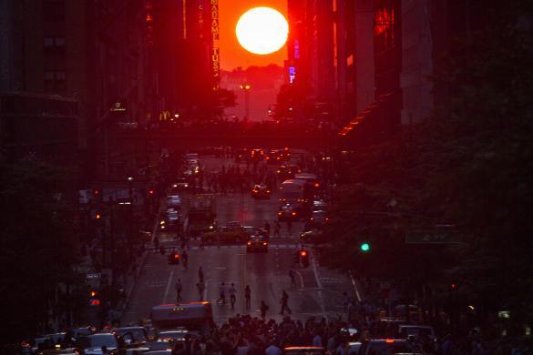 """Mọi người tập trung chụp ảnh hiện tượng """"Manhattanhenge"""" – khi mặt trời di chuyển vào đúng trục đường chính của Manhattan ở New York, Mỹ."""
