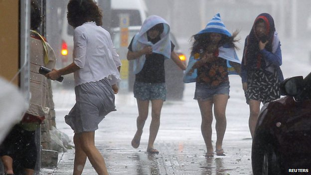 Mọi người đi dưới mưa lớn do siêu bão gây ra Neoguri trên đảo Okinawa, Nhật Bản.