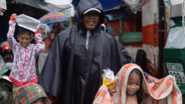 Một người đàn ông dẫn các con đi sơ tán tại thủ đô Manila.
