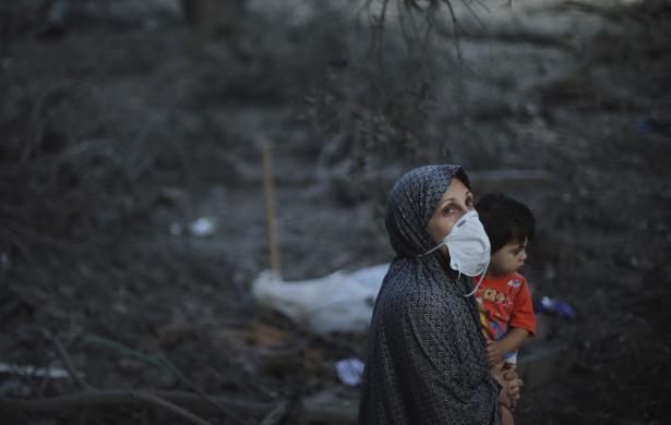 Một phụ nữ người Palestine đeo khẩu trang bế con trai nhỏ khi đứng bên ngoài bị phá hủy trong cuộc không kích của của quân đội Israel vào thành phố Gaza.