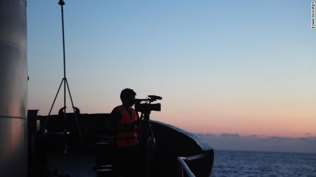 Hình ảnh một người quay phim đang ghi lại hình ảnh từ tàu Cảnh Sát Biển 8003.