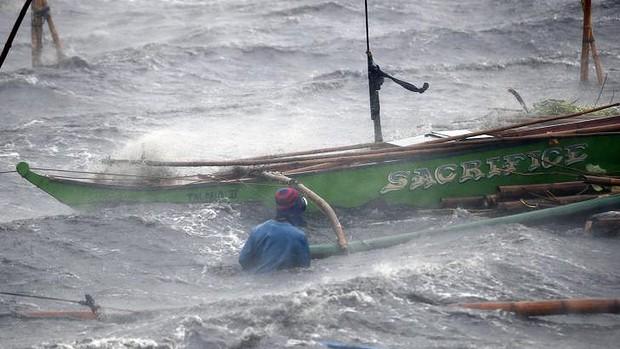 Một ngư dân cố cứu thuyền bị sóng bão đánh trôi ở Imus.