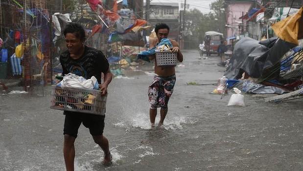 Người dân sơ tán đồ đạc của họ sau khi bão Rammasun  tán phá khu dân cư ở thành phố Imus.