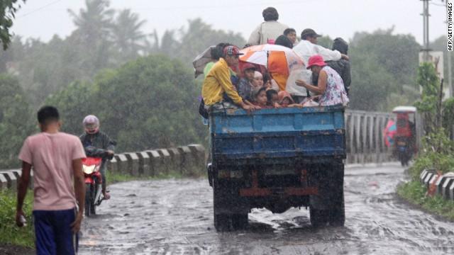 Người dân được đưa đi sơ tán trên một chiếc xe tải dưới trời mua lớn ở thành phố Legazpi.