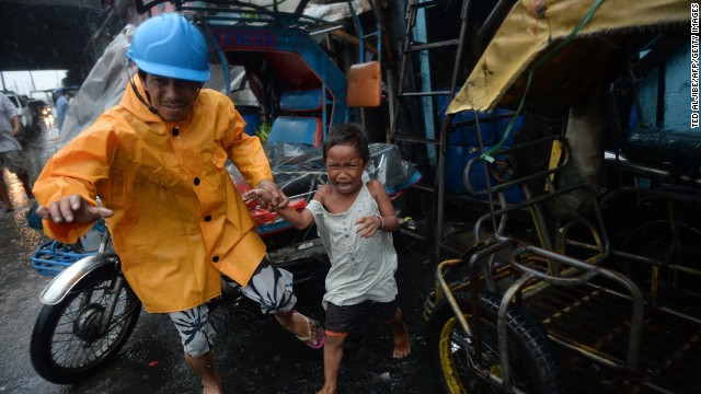 Nhân viên cứu hộ dẫn một cậu bé sơ tán khỏi nhà tại khu ổ chuột ở thủ đô Manila, khi siêu bão gây Rammasun mưa lớn tại nhiều vùng của Philippines.