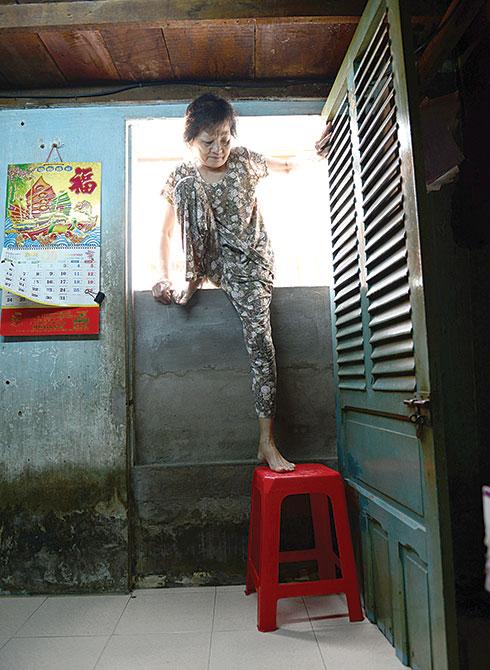 Bà Nguyễn Thị Hoài đặt ghế nhựa ngay cửa để lên xuống nhưng vẫn rất thấp so với mặt đường