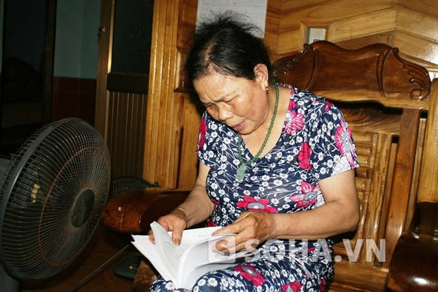 Bà Phạm Thị Mừng cầm trên tay bệnh án và đơn thuốc của chồng