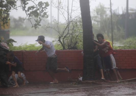 Người dân phải ôm cây để tránh bị gió thổi bay ở Manila.
