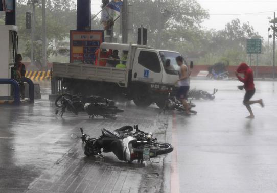 Gió mạnh thổi bay xe máy ở thủ đô Manila.