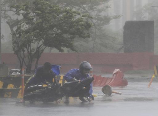 Người dân chống chọi với gió mạnh ở Manila.