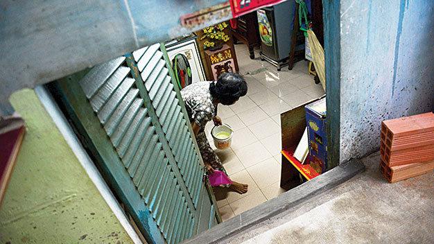 Sau mỗi cơn mưa, bà Nguyễn Thị Hoài phải múc nước trong nhà đổ ra ngoài. Nước tràn vào nhà là do đường cao hơn nền nhà trên 1m!