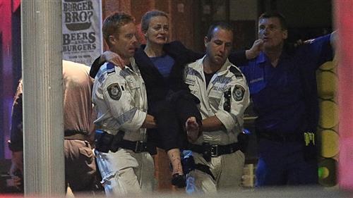 Người phụ nữ bị thương được các nhân viên cứu hộ đưa ra ngoài.