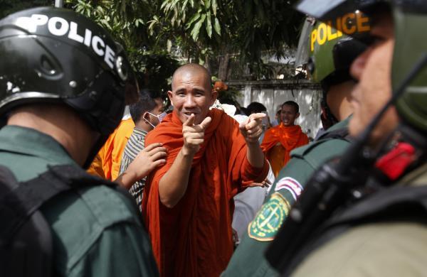 Nhà sư chỉ tay vào cảnh sát chống bạo động trong khi tham gia biểu tình ở Phnom Penh, Campuchia.
