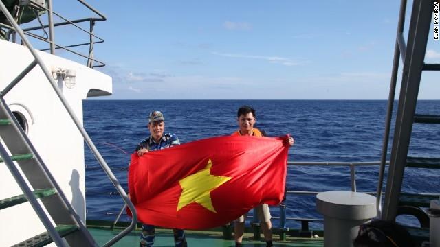 Phóng viên Việt Nam và thành viên thủy thủ đoàn trên tàu Cảnh Sát Biển Việt Nam 8003 đang thể hiện sự trung thành với Tổ quốc.