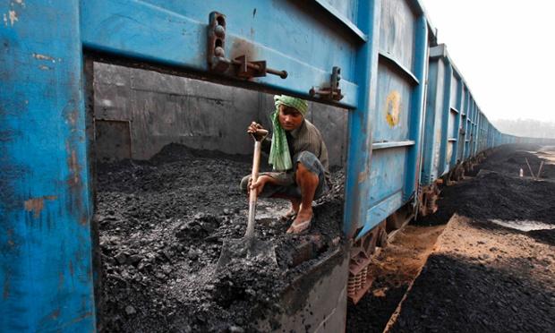 Công nhân xúc than khỏi một toa tàu vận tải tại một nhà ga ở Chandigarh, Ấn Độ.