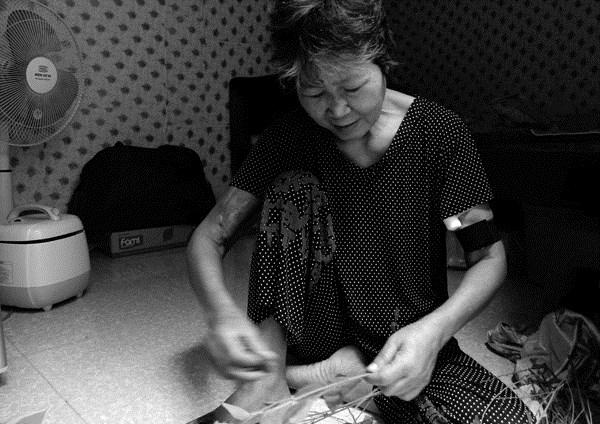 """Cô Đinh Thị Bắc (Quảng Ninh) đang nhặt rau nấu cơm. Cô bảo: """"Chục năm nay ở một mình, cũng quen rồi""""."""