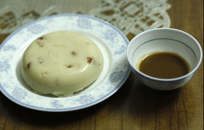 Bánh đúc gạo quê được rắc lên các gia vị như: đậu phộng rang giã dập, đậu xanh, lá hẹ xắt nhỏ mỏng,… ăn kèm với rau thơn và thịt heo ba chỉ chấm mắm cái rất đậm đà.