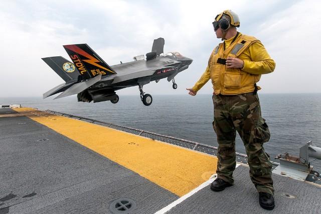 Trong quá trình hạ cánh thẳng đứng, luồng phản lực từ động cơ của F-35B hướng thẳng xuống mặt đất với nhiệt độ hơn 900 độ C.