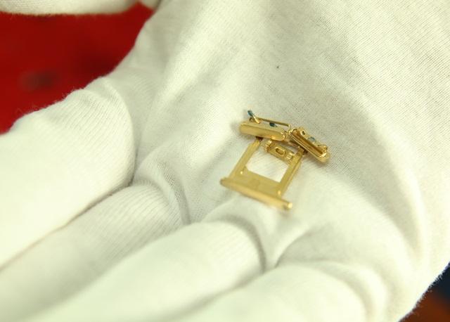 Các chi tiết nhỏ như khay đựng sim, 2 con ốc bên ngoài máy, nút tăng âm, nút gạt rung cũng được nhúng trong bể vàng