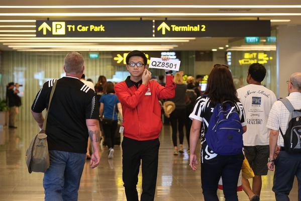Nhân viên sân bay Singapore cầm biển ghi số hiệu chiếc máy bay mất tích để hướng dẫn người thân của các hành khách trên chuyến bay tới khu hỗ trợ đặc biệt.