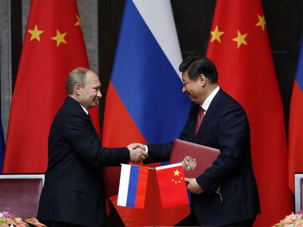 Hai nhà lãnh đạo Nga-Trung tay bắt mặt mừng sau khi đi đến thỏa thuận khí đốt trị giá 400 tỉ USD trong khuôn khổ diễn đàn APEC 2014 Ảnh: AP