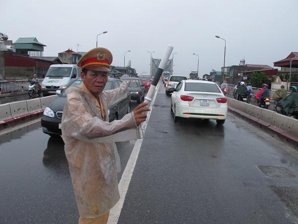 Thượng tá Lê Đức Đoàn tham gia phân luồng giao thông trong những ngày mưa tại chốt cầu Chương Dương