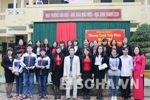 Tập thể giáo viên nhà trường cùng các em học sinh nhận sách từ lãnh đạo Báo.