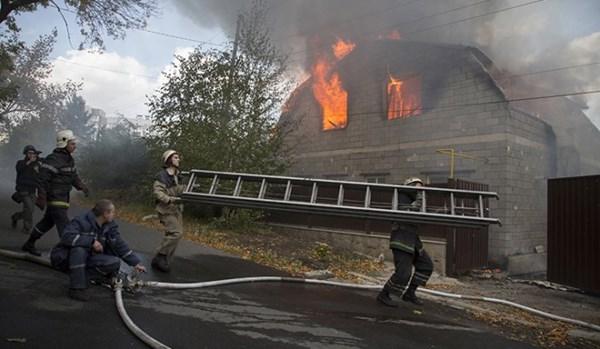 Các nhân viên cứu hỏa hối hả dập đám cháy do ngôi nhà bị trúng pháo kích tại Donetsk.