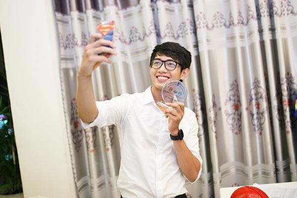 Quang Đăng diện áo sơmi trắng và quần tây hoạ tiết kẻ sọc giống như thời còn ngồi ghế nhà trường.