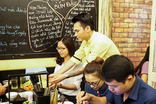 Sau vài phút trò chuyện cũng như chụp hình lưu niệm với khách, Khắc Việt bắt đầu ghi chép món ăn khách yêu cầu và lập tức vào bếp chuẩn bị.