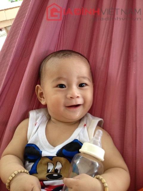 Hình ảnh bé Quốc Huy cười tươi sau khi bú xong bình sữa