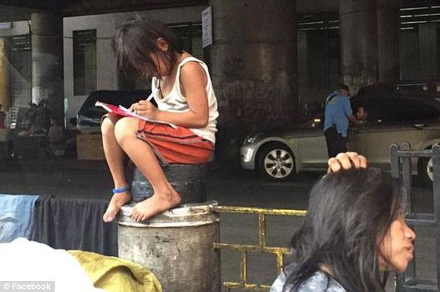 Bé gái Cielo Gonzales mải mê làm bài tập trên trụ lan can chắn đường .