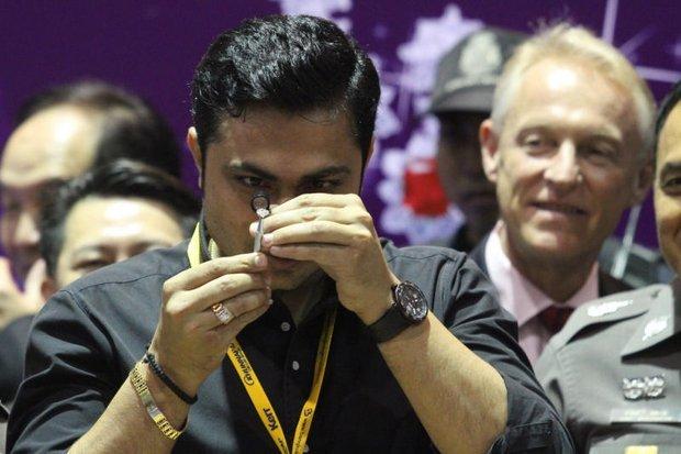 Chuyên gia đá quý thẩm định viên kim cương được lấy ra từ trong bụng của nghi phạm Khương - Ảnh: Bangkok Post